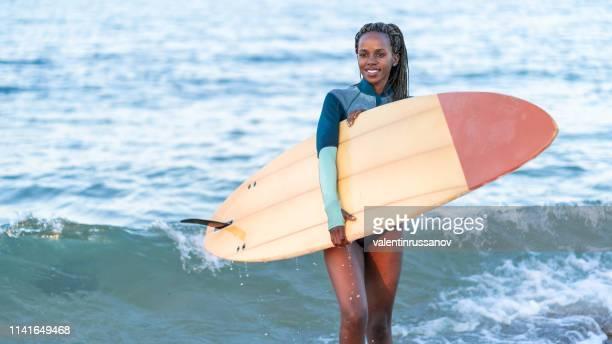 afro surfer chica caminando por el mar y llevar tabla de surf - deporte acuático fotografías e imágenes de stock