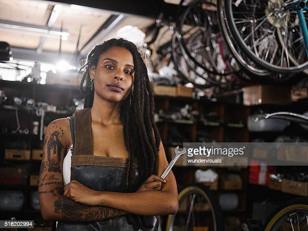 Afro woman bicycle mechanic looking proud in bike repair worksho