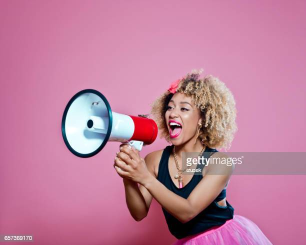 afro woman holding screaming into megaphone - shouting stock photos and pictures