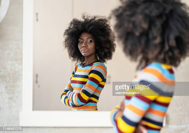 afro woman looking at her reflection in the mirror - looking stock pictures, royalty-free photos & images