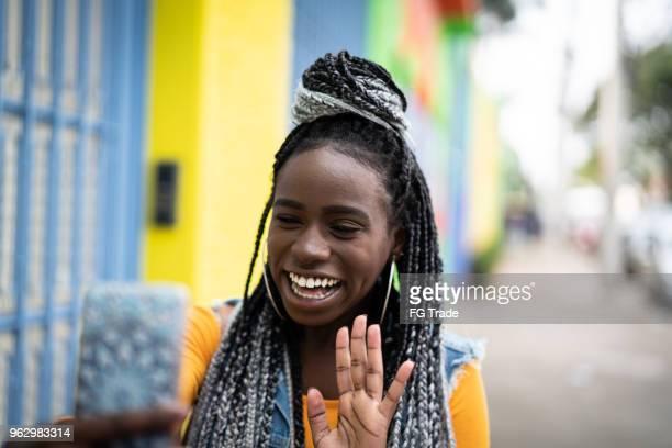 mulher afro, fazendo um vídeo chat no celular - photo messaging - fotografias e filmes do acervo