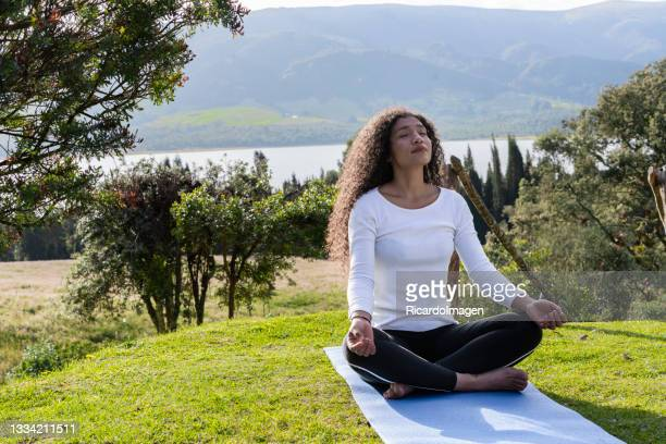 afro woman of average age of 25 years is in nature doing yoga exercises - 25 29 years stock pictures, royalty-free photos & images