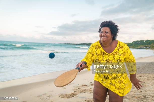 afro woman playing beach tennis - fat woman at beach stock pictures, royalty-free photos & images