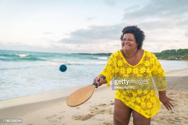 afro frau spielt strandtennis - dicke frauen am strand stock-fotos und bilder