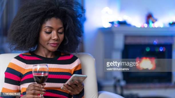 afro woman spending new year's eve at home, drinking red wine and texting friends during quarantine - 25 29 years stock pictures, royalty-free photos & images