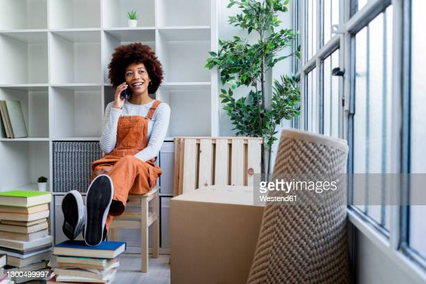 afro woman talking on smart phone while sitting against bookshelf in new apartment - dungarees stock pictures, royalty-free photos & images