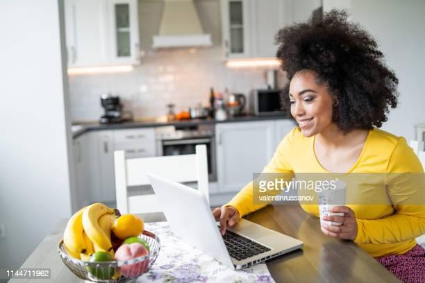 mulher afro que usa o portátil em casa e no café bebendo - responder - fotografias e filmes do acervo