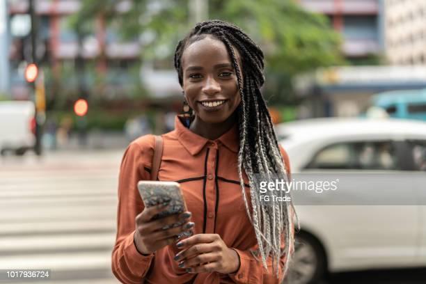 afro vrouw met behulp van mobiele op straat - mobile stockfoto's en -beelden