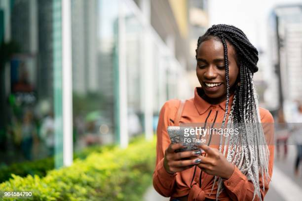 afro woman using mobile at street - good news stock pictures, royalty-free photos & images