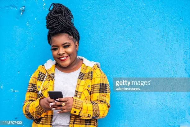 Afro woman using smart phone on a blue background