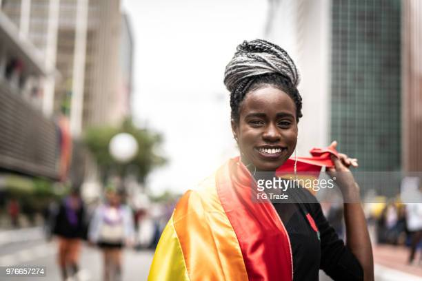 afro woman waving rainbow flag - gay rights stock pictures, royalty-free photos & images