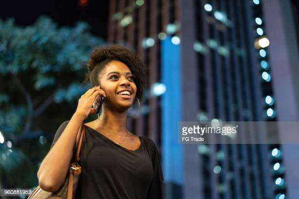 afro young black woman using mobile in urban background - baby mobile stock photos and pictures
