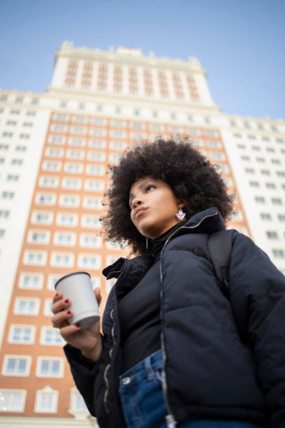 Afro young woman contemplating while holding coffee cup against built structure in city