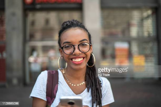 afro young woman in the city using smartphone portrait - alternative lifestyle stock pictures, royalty-free photos & images
