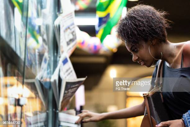 afro young woman looking for the news at newsstand - news stand stock pictures, royalty-free photos & images