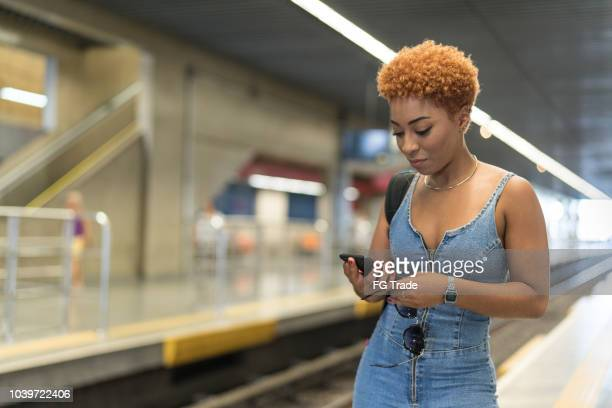 afro young woman using mobile in the subway - candid forum stock pictures, royalty-free photos & images