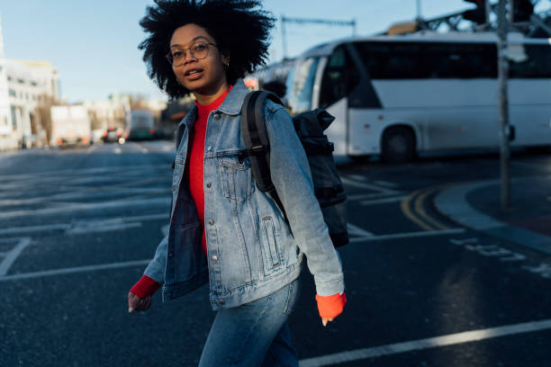 Afro young woman wearing denim jacket crossing road in city