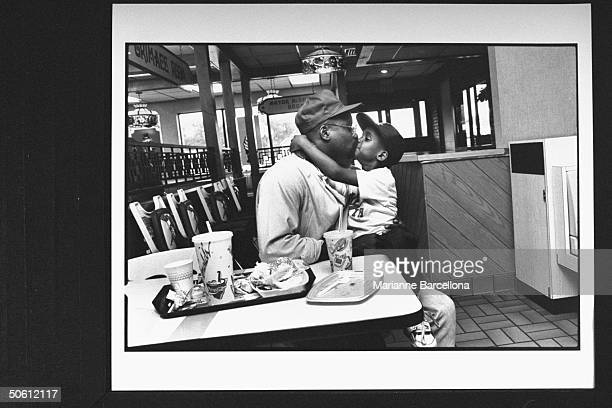 AfroAmer single father cartoonist Joe Young Jr kissing his 6yrold son Kyle who is sitting on his lap while eating at McDonalds Young decided to raise...