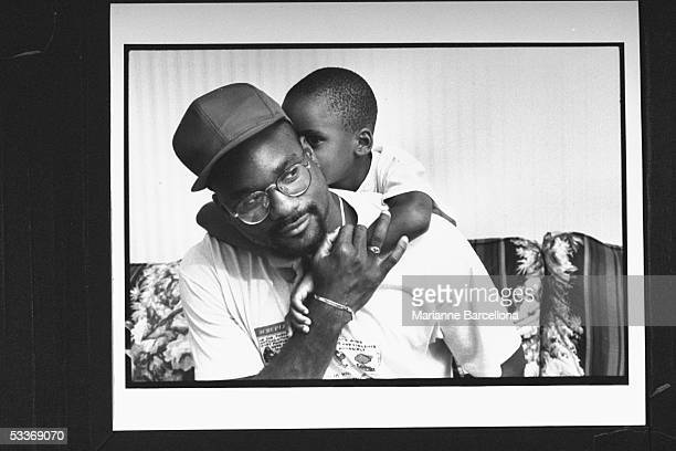 AfroAmer single father cartoonist Joe Young Jr with 6yrold son Kyle who is giving him a hug from behind at home Young decided to raise Kyle on his...