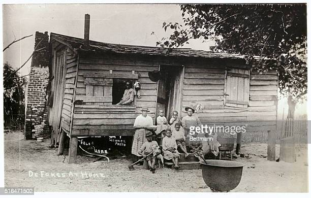 Afro-American family outside of their wooden cabin.