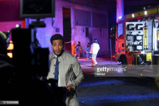 afro-american male reporter covering the fire - american tv presenters stock pictures, royalty-free photos & images