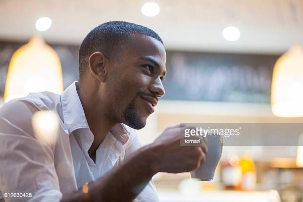 Afro-american man enjoying big cup of coffee