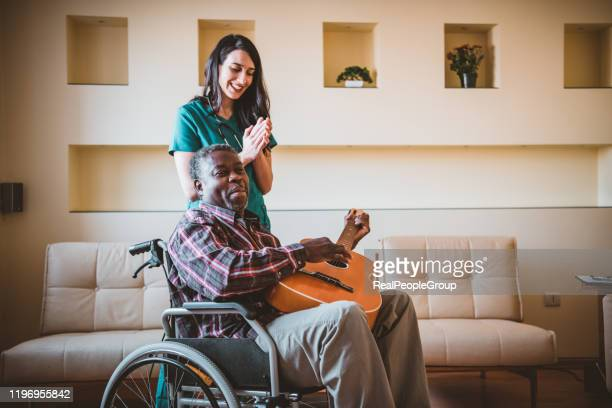 afro-american man in wheelchairs is playing guitar for a female doctor at home - community care stock pictures, royalty-free photos & images