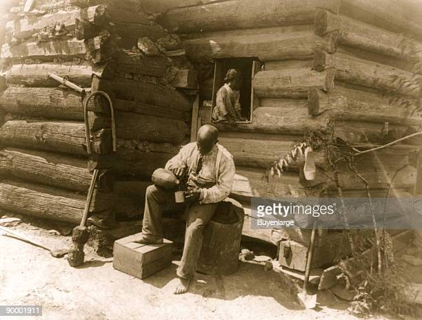 Afro-American man seated outside log cabin, pouring drink into cup and girl seated in window of the cabin