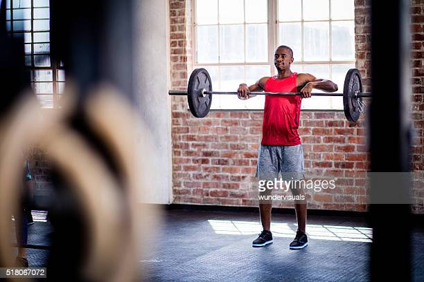 Afro-American man training with barbell weights at the gym
