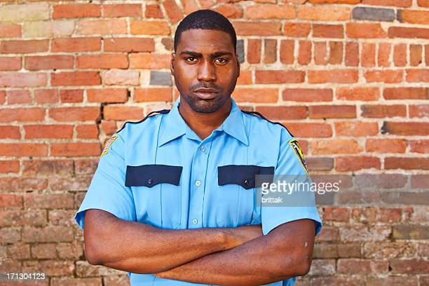 Afroamerican security guard in front of old brick wall.