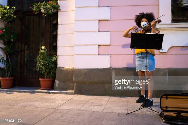 afro-american street musicians wearing face masks playing music in time of pandemic - street artist stock pictures, royalty-free photos & images