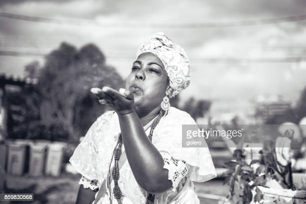 afro-brazilian woman in religious costume blowing powder out of hand