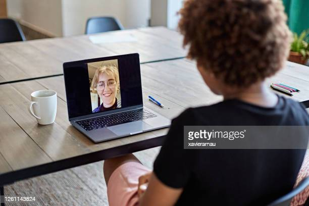afro-caribbean businesswoman on video call with coworker - looking over shoulder stock pictures, royalty-free photos & images