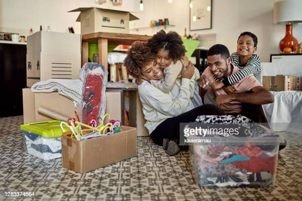 afro-caribbean family relaxing in new home on moving day - afro caribbean ethnicity stock pictures, royalty-free photos & images