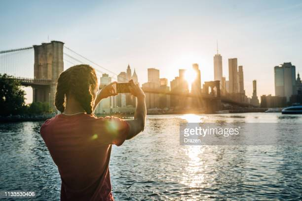 afro-caraïbe, touriste hispanique à new york, prenant un coup de manhattan au coucher du soleil - amérique du nord photos et images de collection