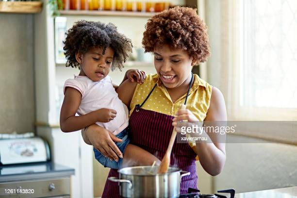 afro-caribbean mother and 3 year old daughter cooking pasta - afro caribbean ethnicity stock pictures, royalty-free photos & images