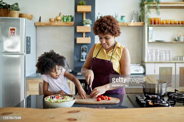afro-caribbean mother and young daughter cooking together - condition stock pictures, royalty-free photos & images