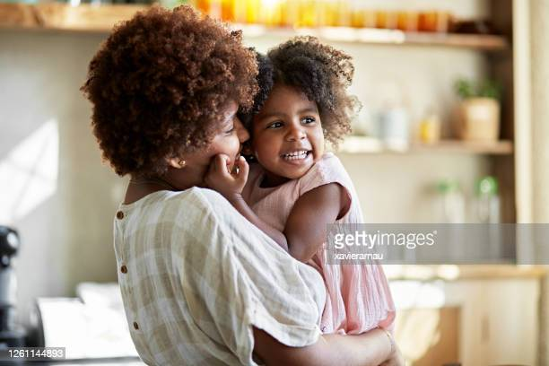 afro-caribbean mother and young daughter showing affection - afro caribbean ethnicity stock pictures, royalty-free photos & images