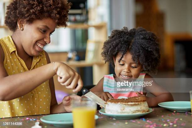 afro-caribbean mother cutting birthday cake for daughter - cake stock pictures, royalty-free photos & images