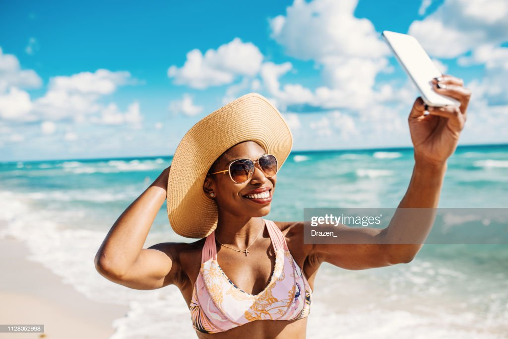 Afro-Caribbean woman enjoys summer at the beach in USA : Stock Photo
