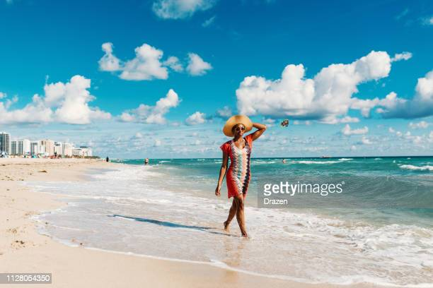 afro-caribbean woman enjoys summer at the beach in usa - miami beach stock pictures, royalty-free photos & images