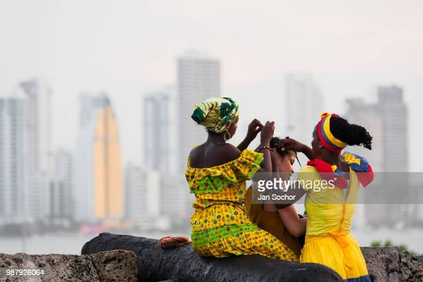 AfroColombian girls dressed in the traditional palenquera costume create a braided hairstyle for a female tourist on the stone walls on December 11...