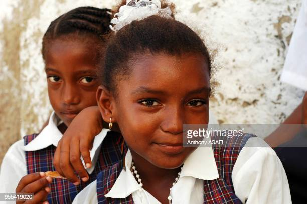 Afro-colombian schoolgirl smiling with a friend in the background against a wall, Tierrabomba, Colombia.