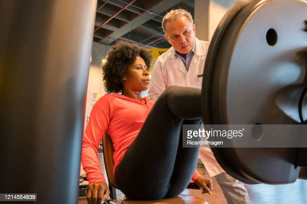 afro-colombian woman with her doctor in a gym - sports medicine stock pictures, royalty-free photos & images