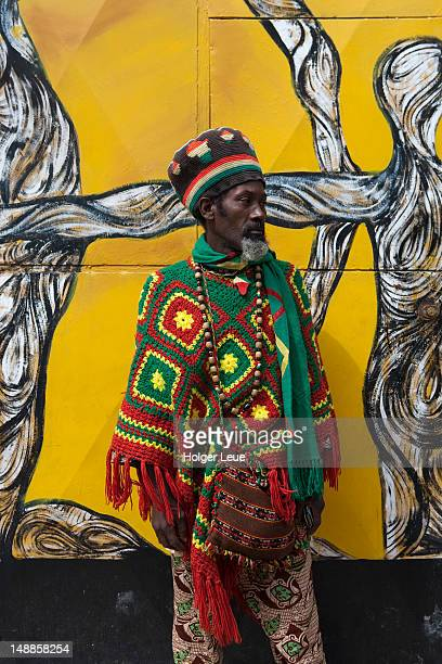 afro-cuban man standing in front of mural wall at callejon de hamel. - callejon stock pictures, royalty-free photos & images
