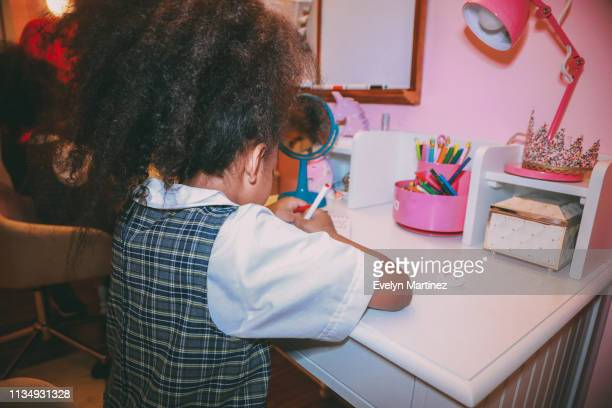 Afrolatina girl at desk, face not visible. Girl is wearing a plaid school uniform. In the background is her desk with a pink desk accessories, a blue mirror, and a dry erase board.