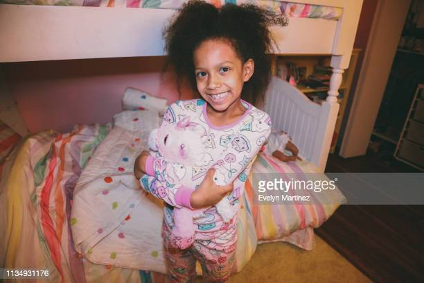 afrolatina girl holding stuff animal, standing by a bunk bed. bookcase and closet in the background. - evelyn martinez stock pictures, royalty-free photos & images