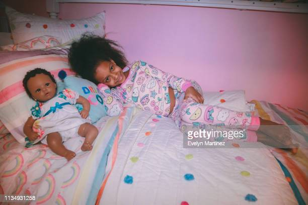 Afrolatina girl in her pajamas on a bed. Pillows and baby doll in the frame. Pink wall in the background.