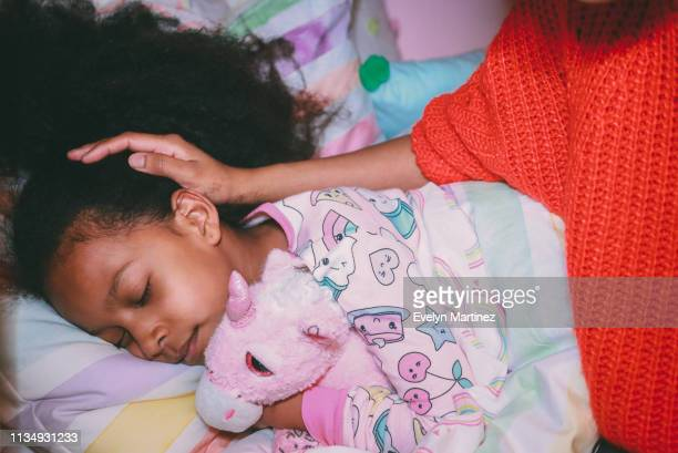 Afrolatina girl in pajamas holding stuffed unicorn with her eyes closed. Mother's face and neck not visible. Mother's hand on daughters head.