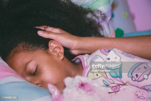 Afrolatina girl in pajamas is holding a stuffed unicorn with her eyes closed. Mother's hand is visible in this close-up.